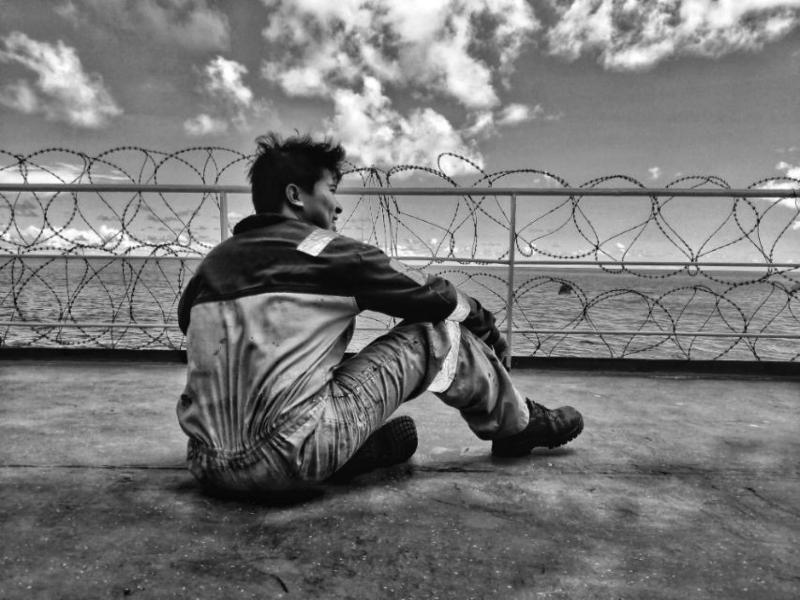 A seafarer on deck looks out to sea