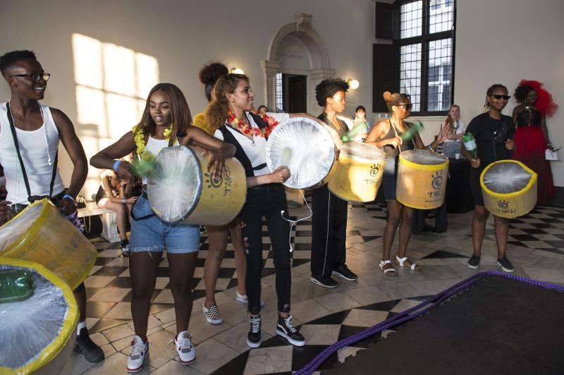 A group of young people playing drums in the queens house