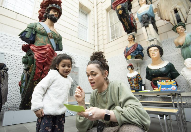 An adult and child are looking at a piece of paper. In the background are figureheads.