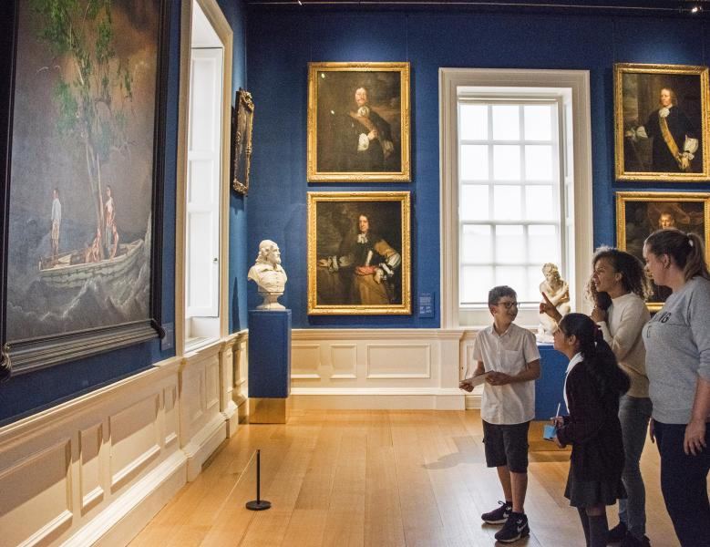 Two children and two adults look at a large image in the Queen's House.