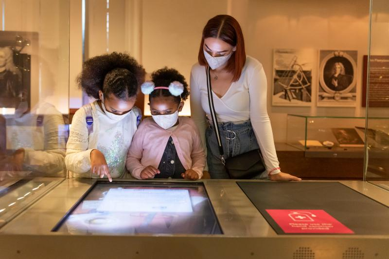 A family looks at an interactive display at the Royal Observatory. They are wearing face masks