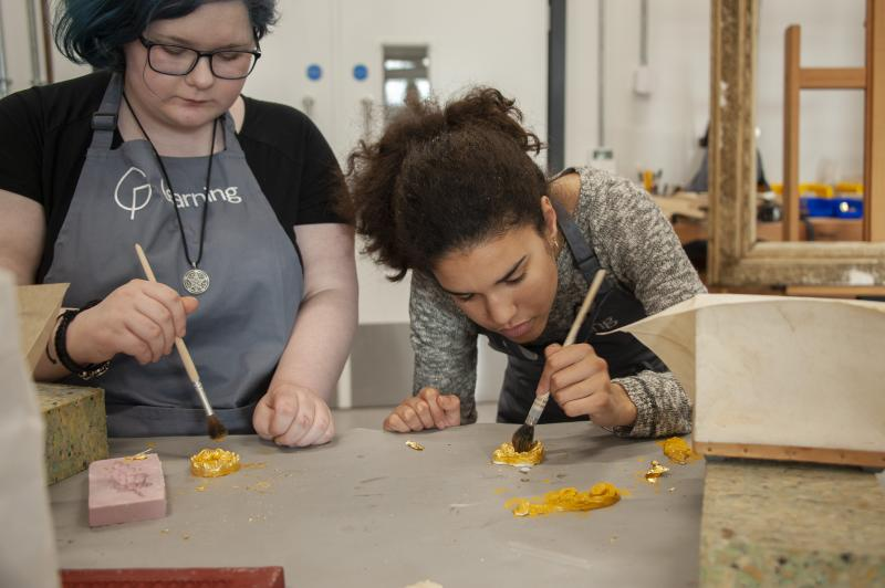 Two young people are painting gold leaf during a work experience placement