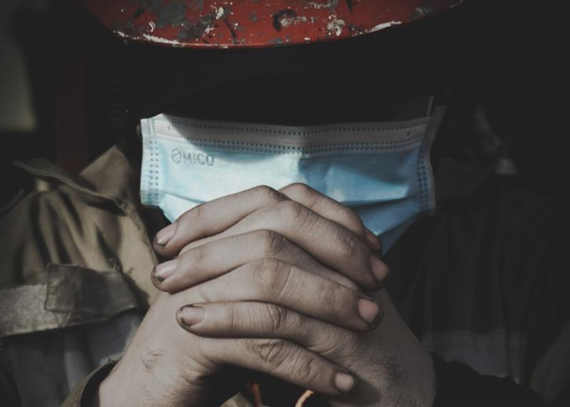 A seafarer clasps his hands in prayer. His face is in shadow, but he is wearing a mask as part of coronavirus safety measures