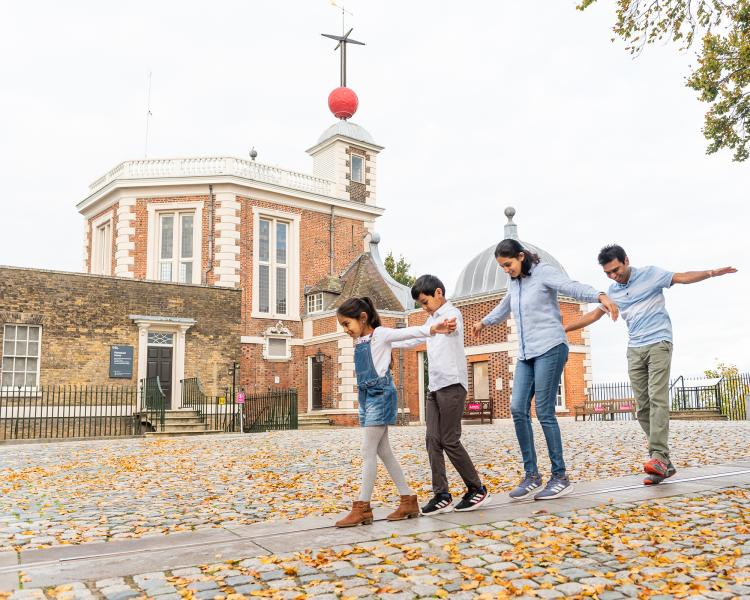 A family plays on the Prime Meridian Line in front of the historic buildings at the Royal Observatory Greenwich