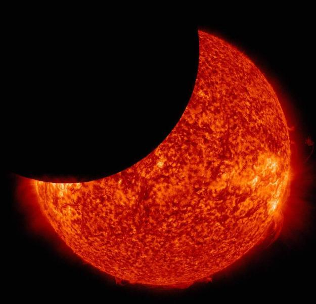 A telescope view of a partial solar eclipse, with the black shadow of the Moon crossing the fiery red disc of the Sun