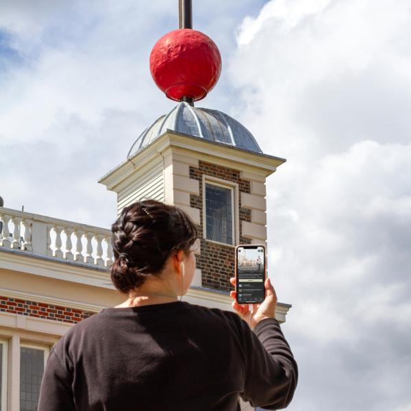 A woman holds her phone as she listens to the Royal Observatory audio tour, with the Observatory buildings in the background