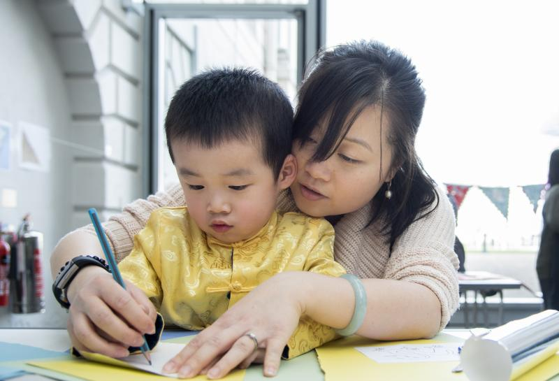 (Source of a mother helping the child to draw using a pencil Picture)