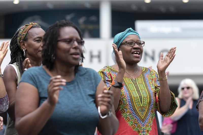 A group of women clap in celebration as they watch a musical performance