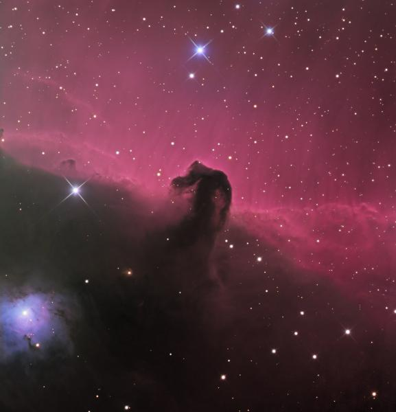 A deep space astrophotograph of the horesehead nebula, with pink curtains of light and bright blue-white pinpricks of stars