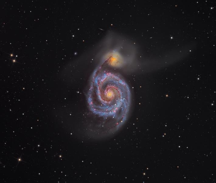 An astronomy photograph showing the M51 'Whirlpool Galaxy'. The galaxy appears as a purple-yellow spiral in the centre of the frame