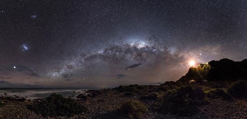 A skyscape at night showing a constellation of stars appearing to point towards a bright lighthouse on the right