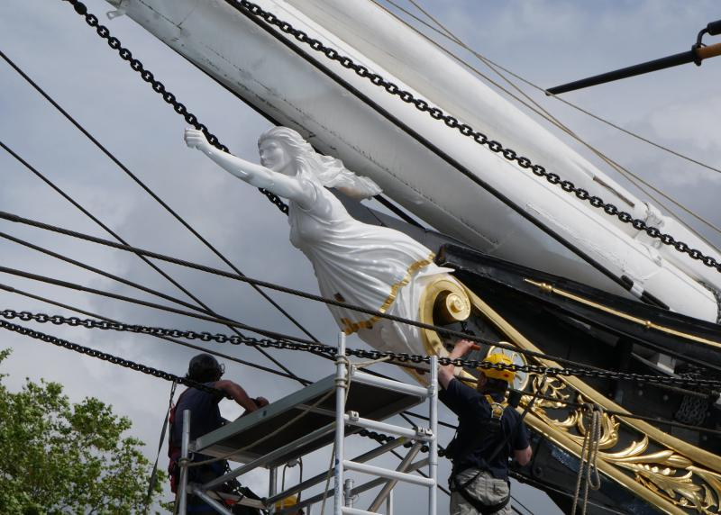 The new figurehead for historic ship Cutty Sark during installation. Workers standing on scaffolding fix the sculpture in place