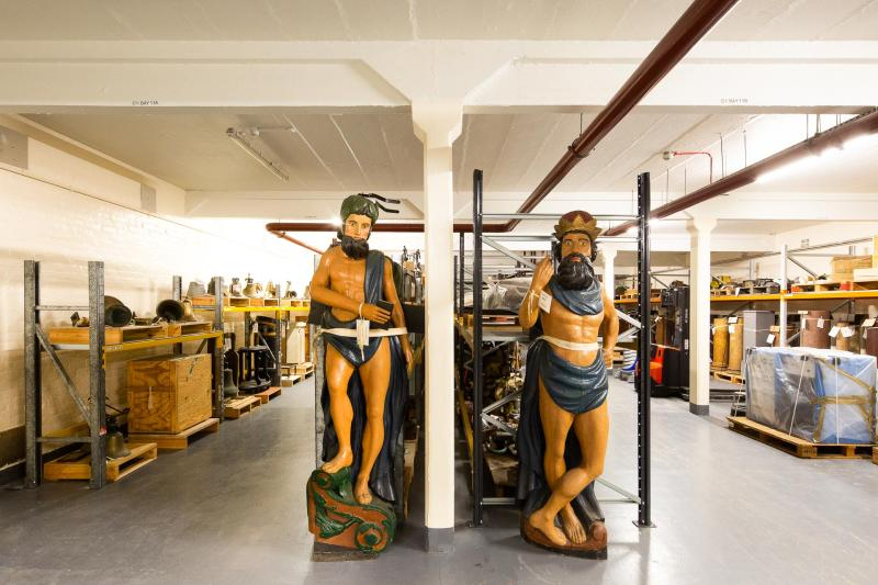 Inside Royal Museums Greenwich collections centre - rows of objects including two ships figureheads