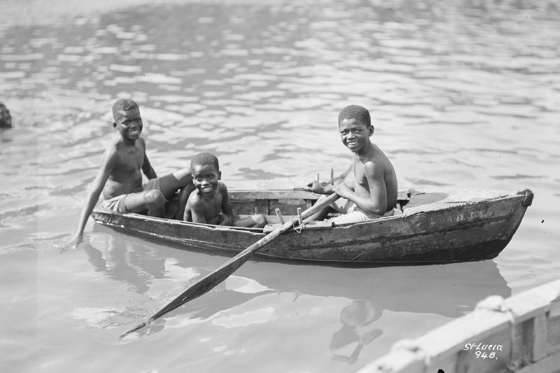 Three small diving boys in a locally constructed wooden rowing boat at Castries, St. Lucia, West Indies (P94762, © National Maritime Museum)