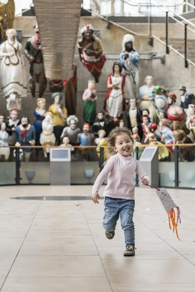 Toddler running in front of the figureheads