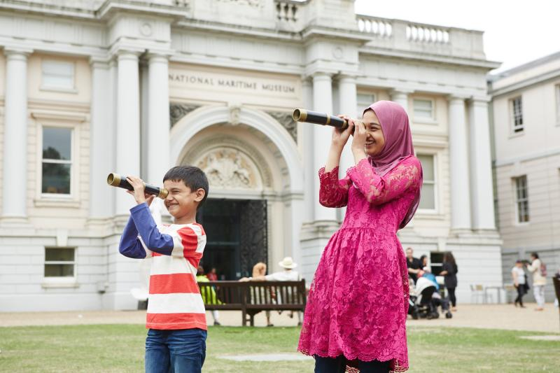 Two children look through telescopes outside the National Maritime Museum