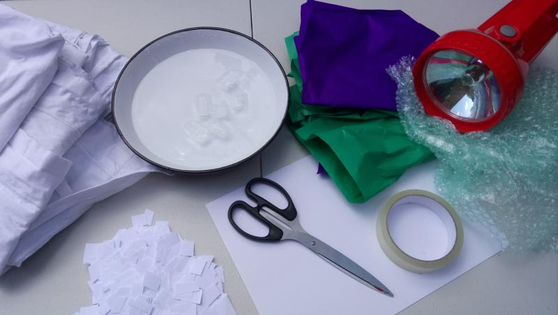 A photo of the materials needed. A bed sheet, bowl of water and ice, scissors, paper, torch, bubble wrap, coloured tissue paper, tape.