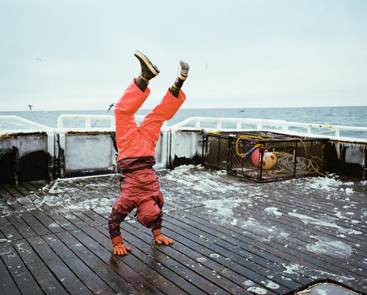 Image shows a man in an orange work suit doing a handstand on an icy deck