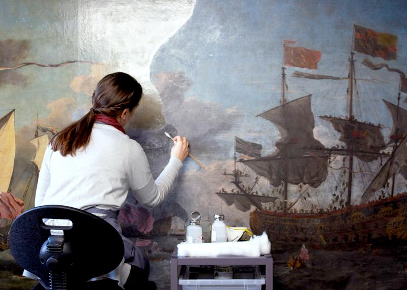 A conservator works on a small portion of a large maritime oil painting