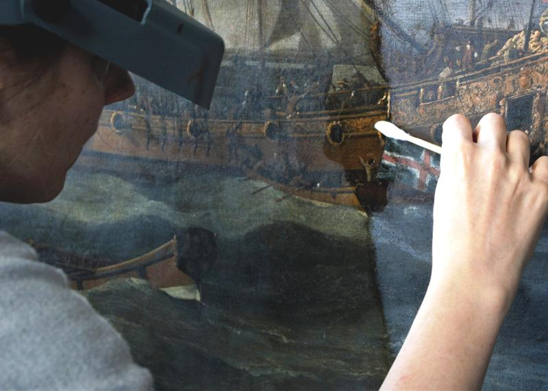 A conservator cleans an oil painting during a conservation project