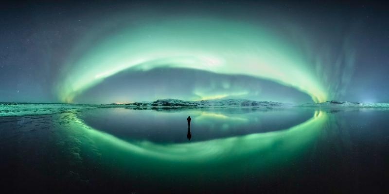 A man stands looking at green bands of aurorae in Iceland