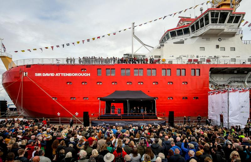 Crowds gather to see the new polar research ship Sir David Attenborough, her red hull bright in the centre of the frame