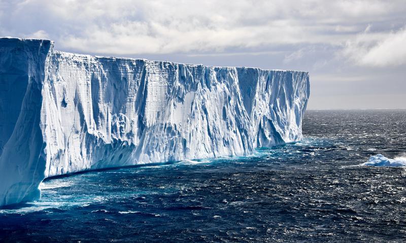 The face of an iceberg falls away to a dark blue ocean