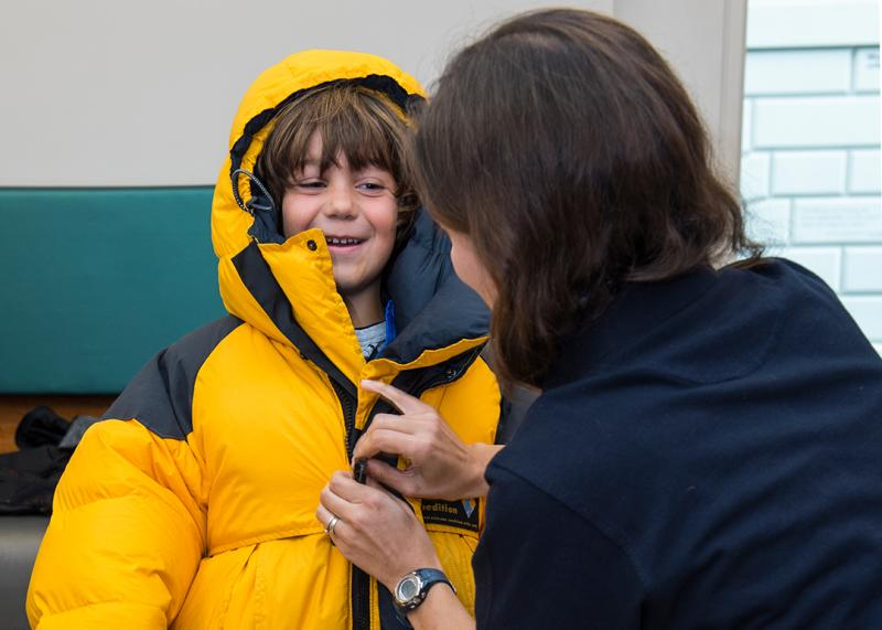 A boy tries out a winter puffer jacket during an event about living in the Antarctic