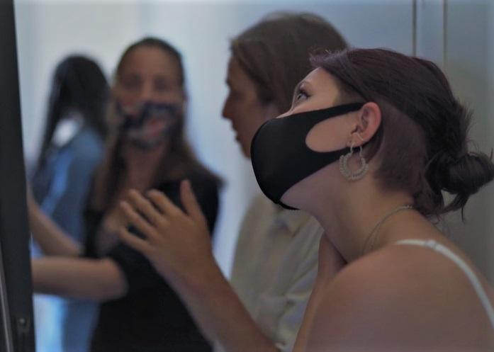 A woman wearing a mask looks up at an object to her left