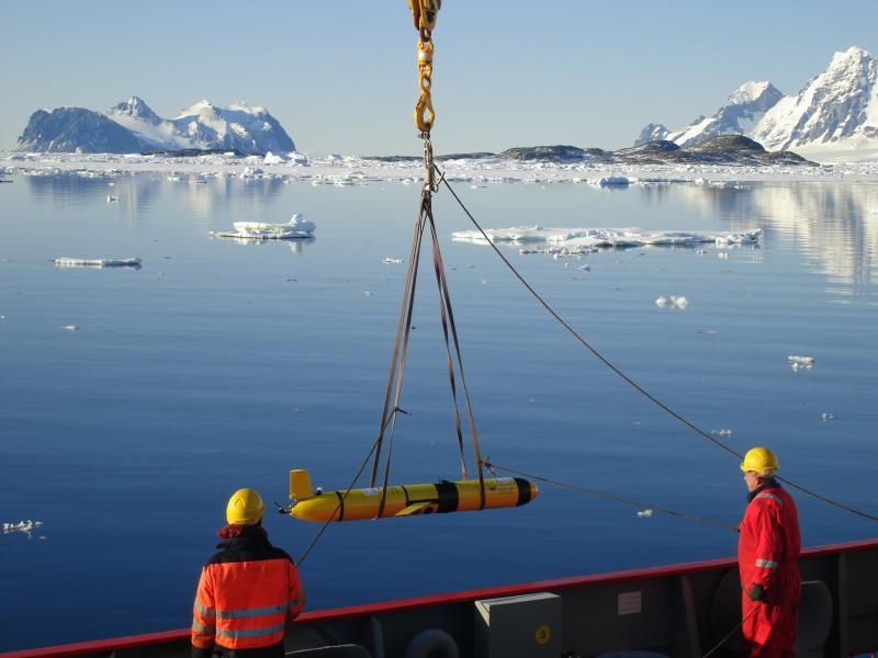 A team lower a polar robotic 'glider' into the water from the deck of a ship, with icebergs in the background