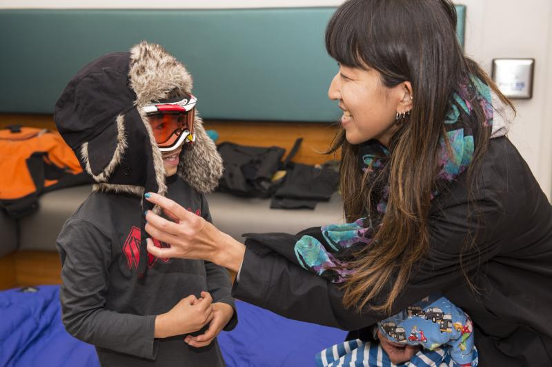 An adult helps a child to get dressed into polar gear