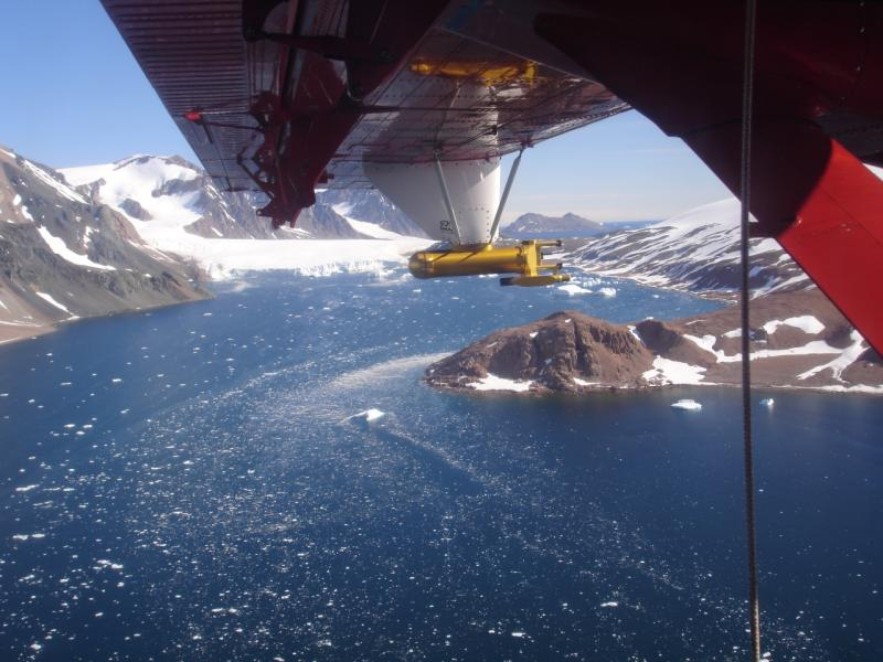 British Antarctic Survey Twin Otter aircraft with Cloud, Aerosol and Precipitation Spectrometer flying over mountainous coast in Antarctica.