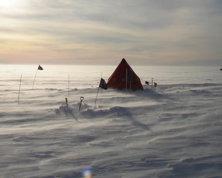 A pyramid tent in shadow pitched on a frozen glacier, with the wind picking up the snow on the ground