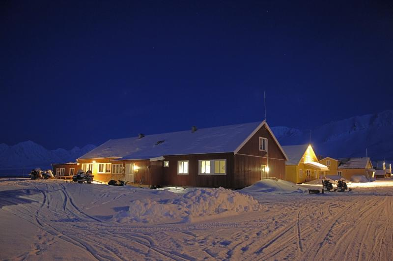 The UK's Arctic station at night. Lights are on in a single-storey wooden building surrounded by snow
