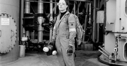 A black and white photo of an oil worker. She wears glasses and overalls, and stands looking at the camera in front of rig pipes