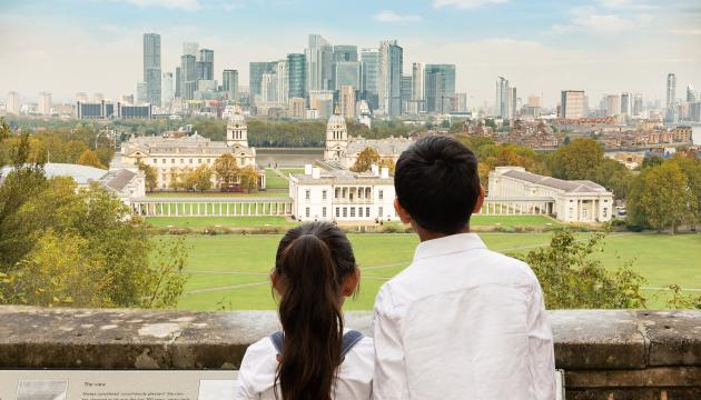 A brother and sister with their back to the camera look out from the viewpoint at the top of Greenwich Park towards historic Greenwich